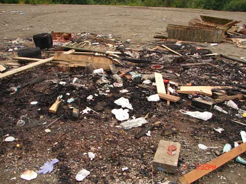 jpg Material dumped off Revilla Rd. for someone to clean up.  Burned pallets have hundreds of nails in them.