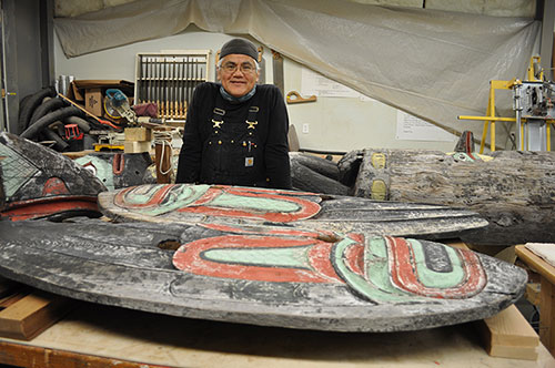 jpg Tlingit Master Carver Wayne Price of Haines stands near the totem he is restoring.