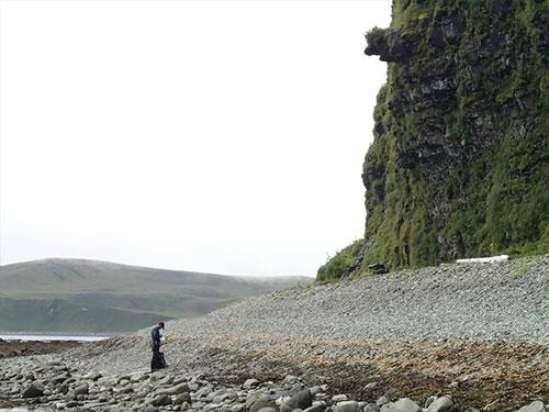 jpg Geologist surveys the steep, coarse beach at the base of a 50 m high sea cliff along the northwest shore of Driftwood Bay, Umnak Island, Alaska.