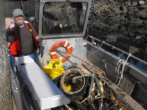 Pat Jirschele on his boat with material collected at Thomas Basin.