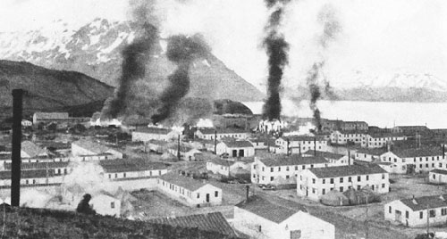 THE DUTCH HARBOR WAR Burning buildings at Ft. Mears after first enemy attack on Dutch Harbor, 3 June 1942