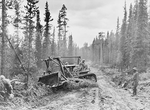 jpg Caterpillar tractor with grader widening the roadway of the Alcan Highway