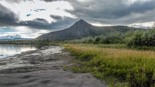 jgp A mountain rises above the Sheenjek River in July.