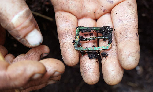 jpg Researchers discovered a brass strap buckle during the excavation.