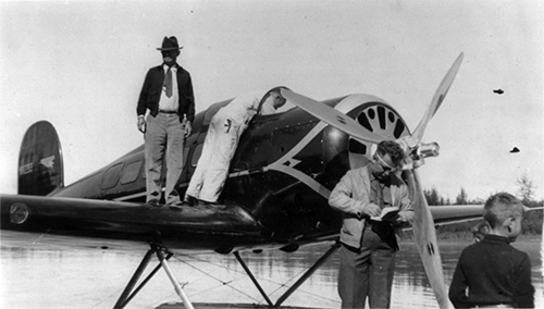 jpg Rogers standing on the wing of the seaplane, with Wiley Post standing in front of the propeller, August 1935 at Fairbanks.