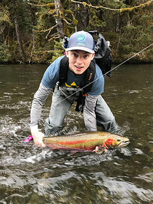 jpg Nick Whicker poses on May 10, 2018 with his first steelhead, caught on the Situk River in Yakutat with a UAS Outdoors studies class taught by professor and Salmon Fellow Kevin Maier. The fish bit onto a fly Whicker had tied that morning (it already had a hook in its tail.) 