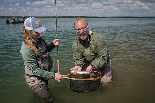 jpg Abbey Whitcomb and her client, Naknek resident Bryon Singly, pose with a small rainbow on the Naknek River.